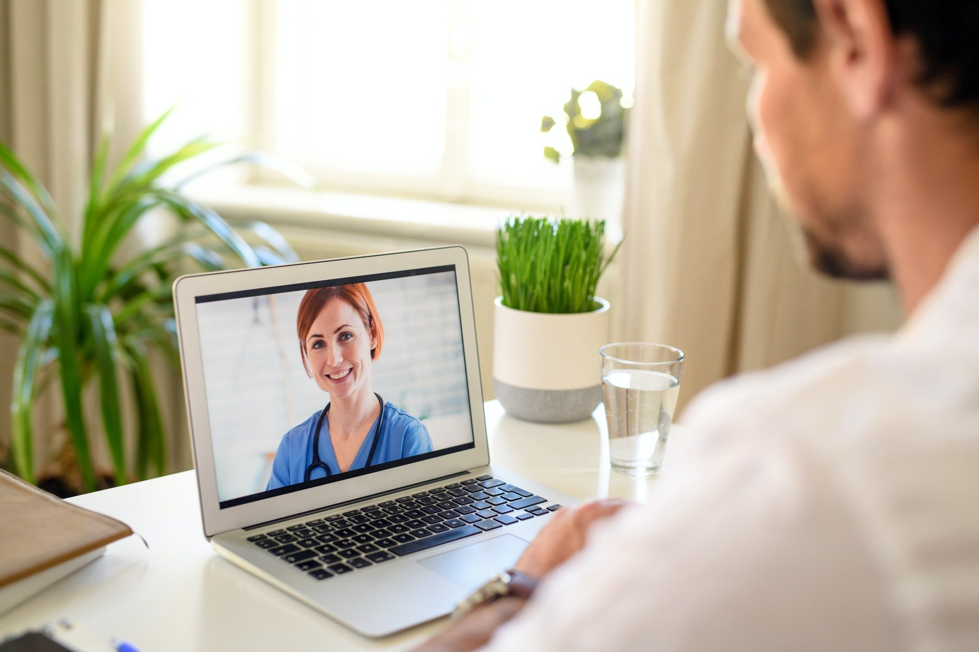 Man having video call with doctor on laptop at home, online consultation concept